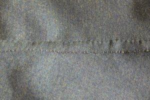Verbindungsnaht mit Rückstich, die Nahtzugabe wird eingeschlagen und auf dem Stoff festgenäht.